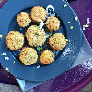 Baked stuffed mushrooms on a pile of dark coloured plates
