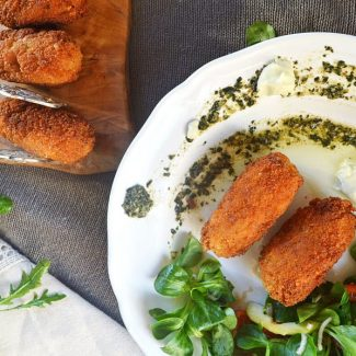 Two browned rice croquettes on a wooden board and two plated with pesto, aioli and salad on a white plate