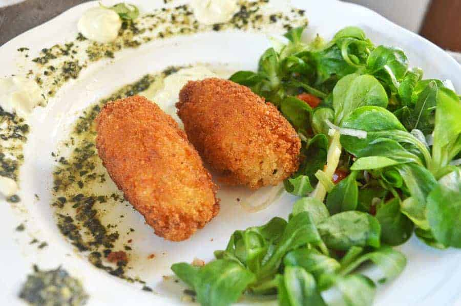 Two golden rice croquettes on a white plate with salad and aioli and pesto
