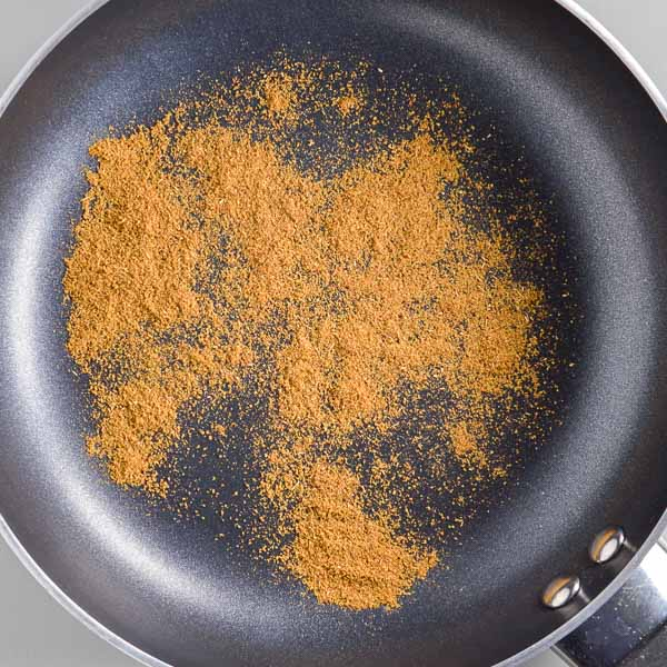 Ground cumin in a small black pan