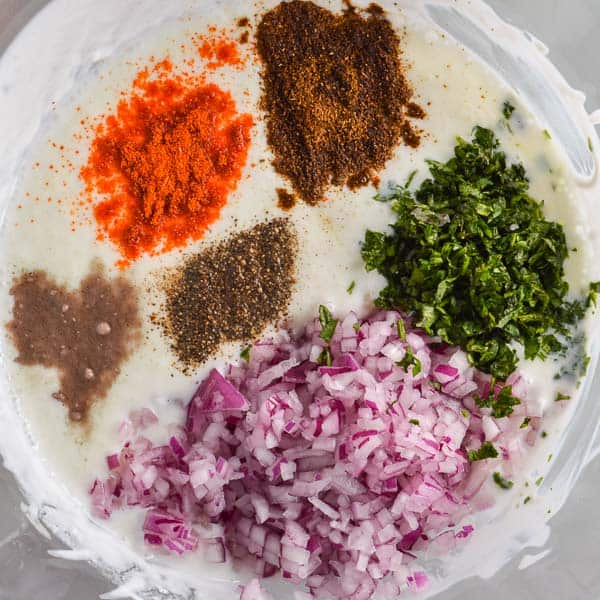 A bowl of yoghurt with spices and chopped red onion and cilantro on top