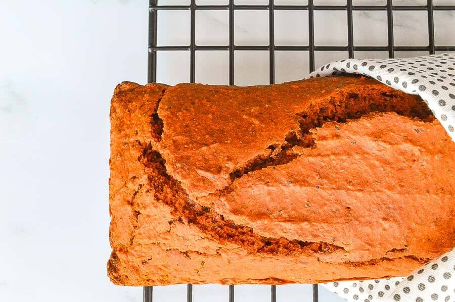 An orange-red bread on a blackcooling grid