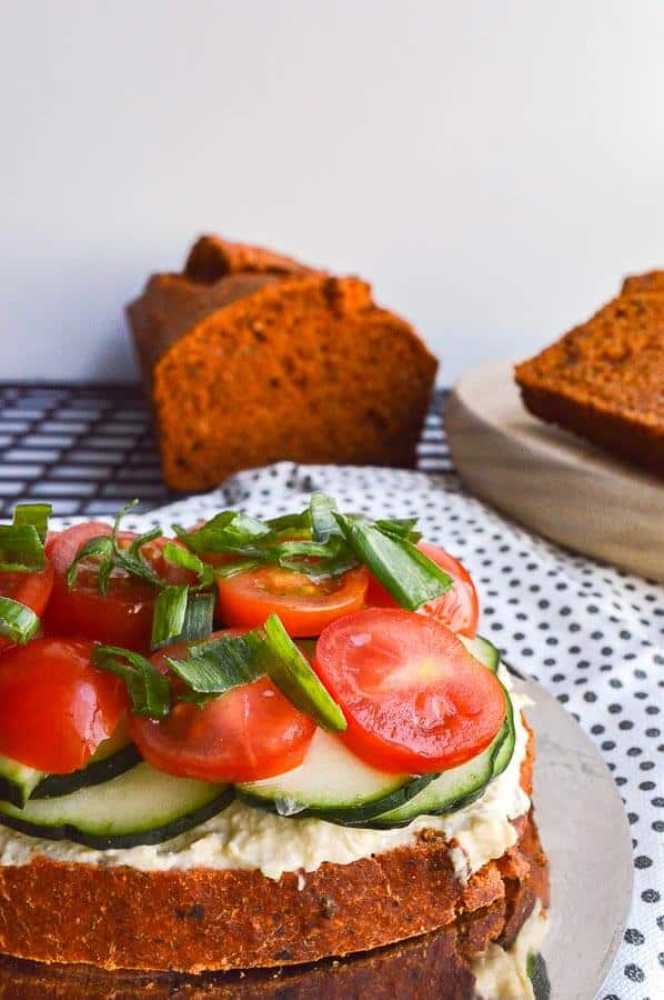 A slice of tomato bread loaded up with tomato, cucumbers and hummus