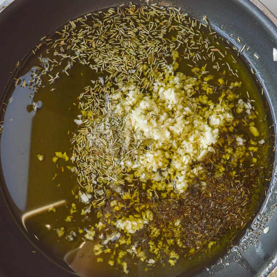 Garlic and herbs in oil in a pan