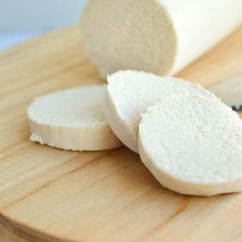 A log of goat cheese half-sliced on a wooden chopping board