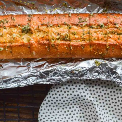 A baguette of garlic bread on aluminum foil with a polla dotted white teatowel