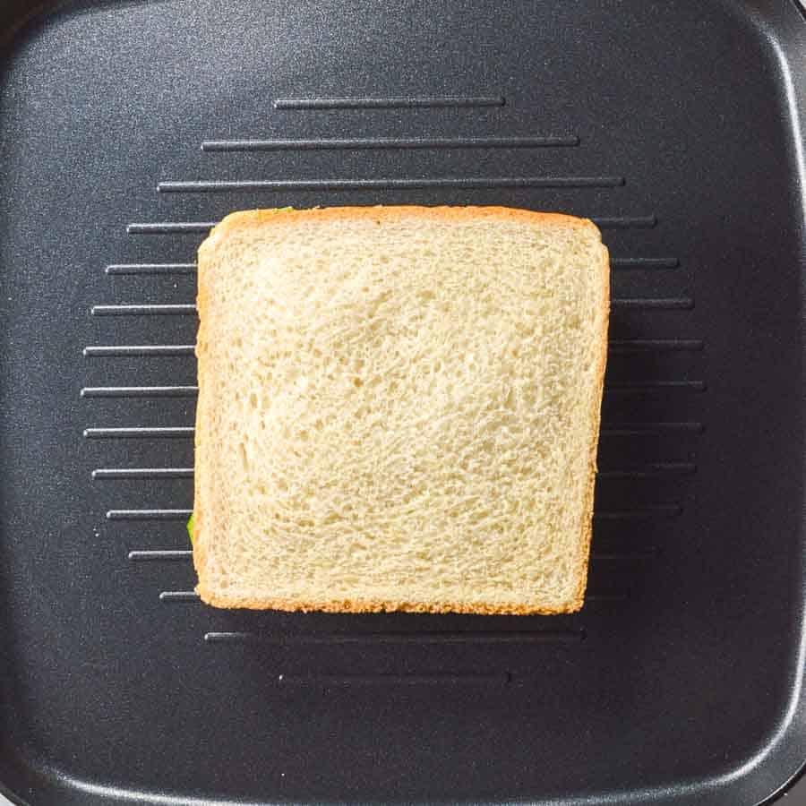 A sandwich on a black grill pan