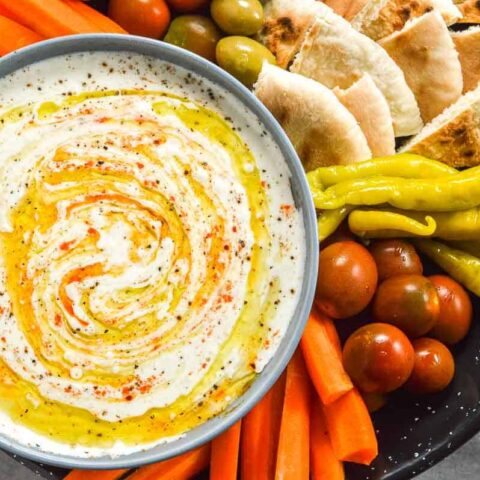 A bowl of feta do[ with chili peppers, carrots and pita