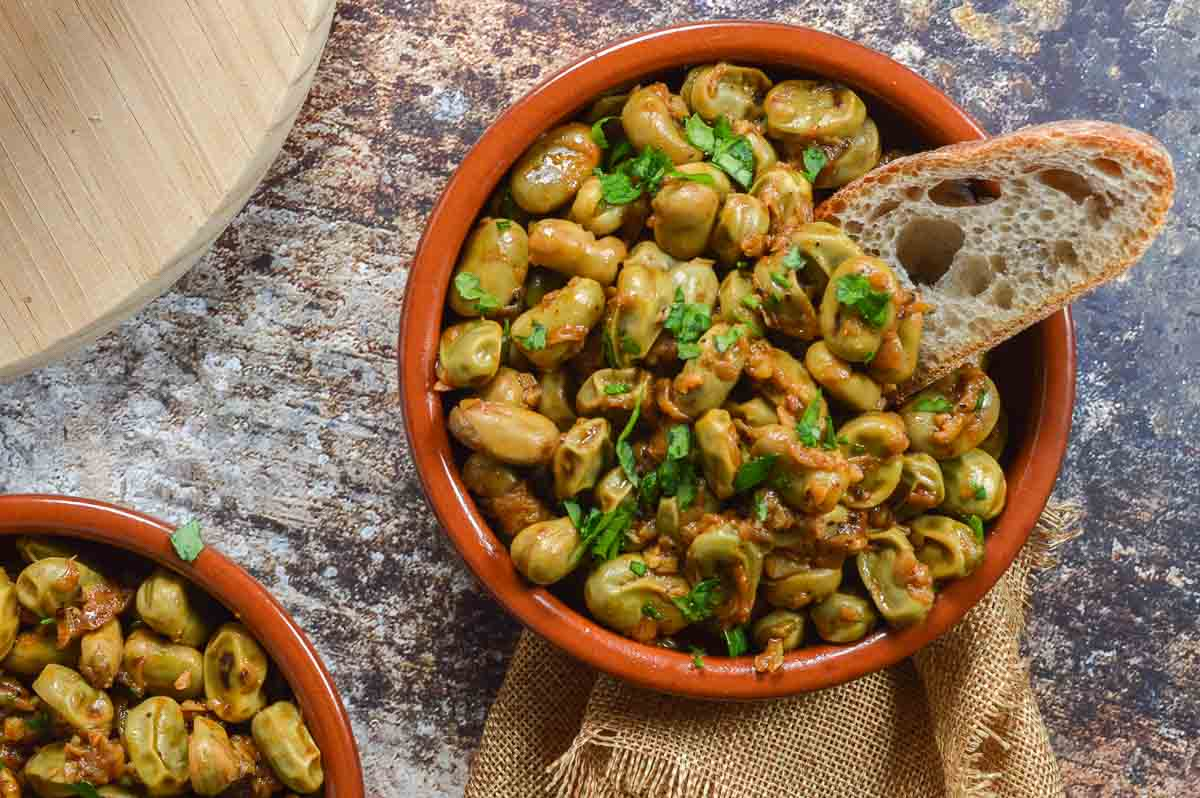 Broad beans in a terracotta tapa dish with bread