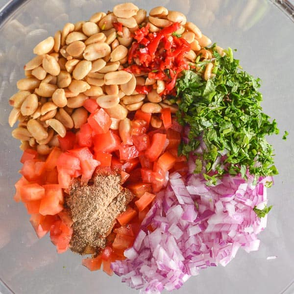 A glass bowl with peanuts, cilantro, red onion and tomatoes