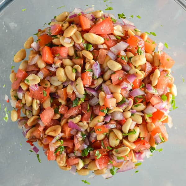 A glass bowl with a mixture of peanuts, tomatoes, fresh cilantro and red onion