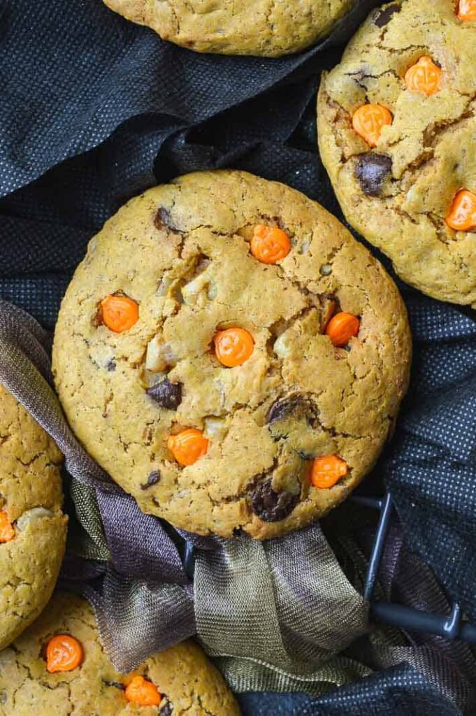 overhead view of chocolate chip cookies with orange halloween sprinkles on black background