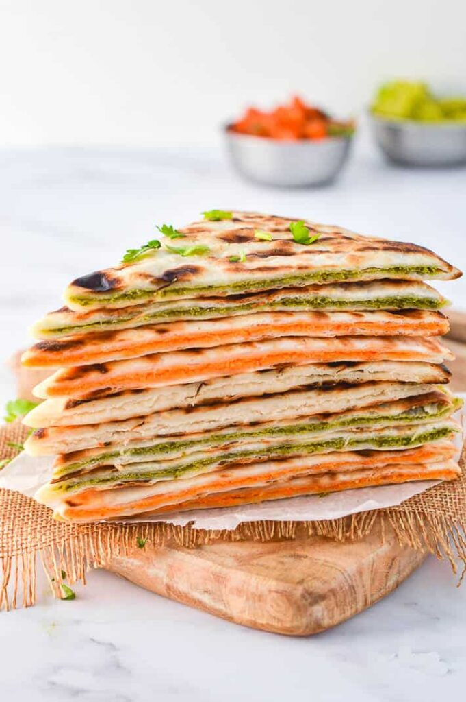 side view of stack of quesadillas with salsa and guacamole in the background