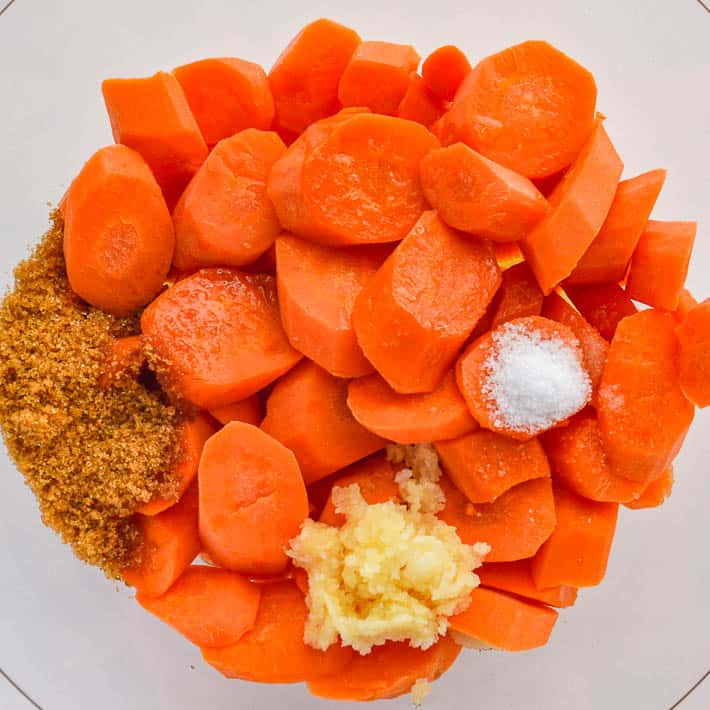 A glass bowl of sliced carrots with garlic brown sugar and salt
