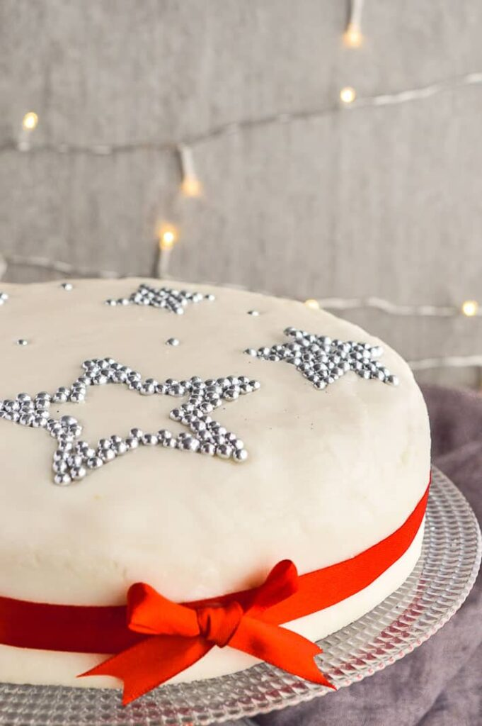 A decorated Christmas cake on a grey background with fairy lights