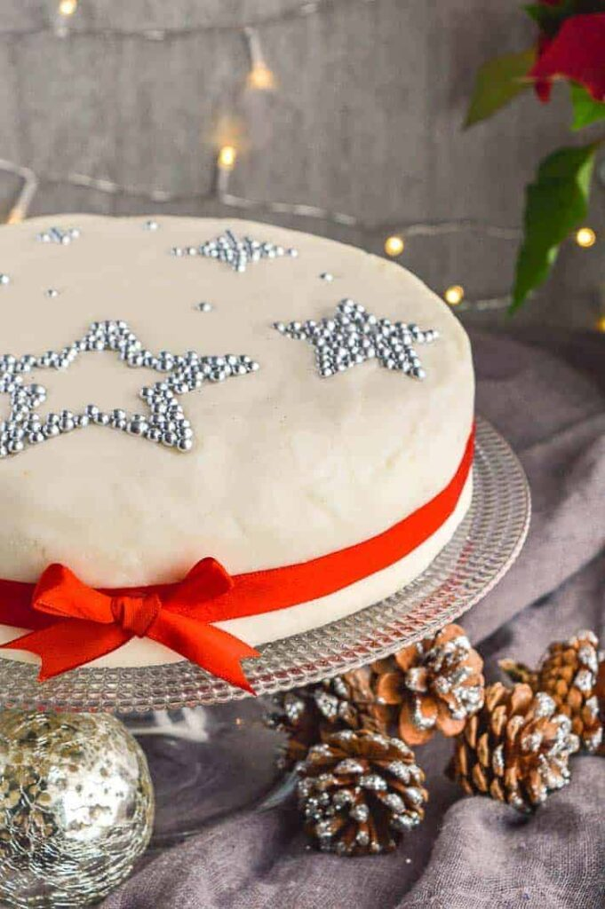 A christmas cake with silver stars and a red ribbon around it