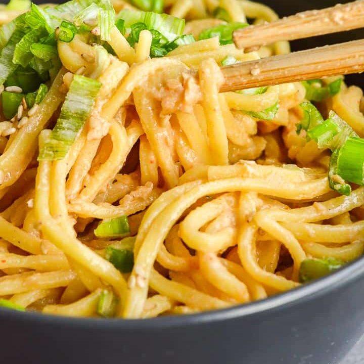 chopsticks picking up creamy sesame garlic noodles form a gray bowlful.